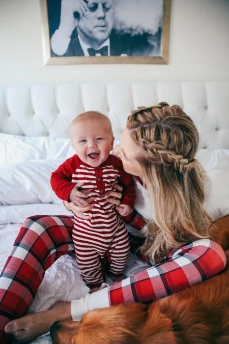 Chica sosteniendo a un bebé mientras ambos están sentados en la cama
