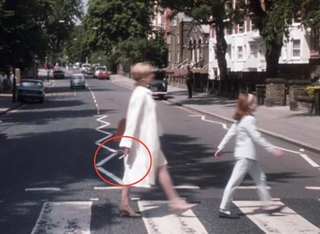 madre y niña caminando mientras cruzan la calle mujer con cigarro