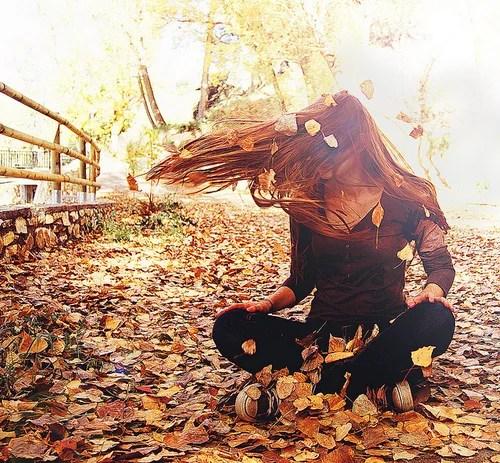 chica jugando en la hojas del parque