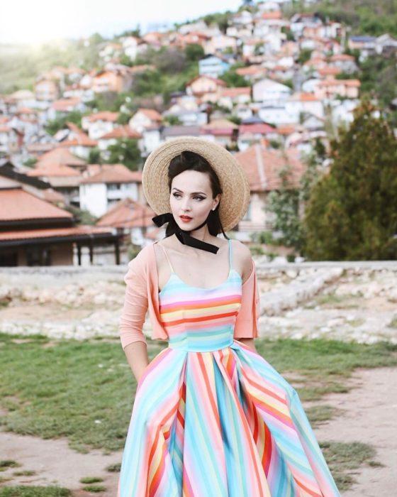 mujer blanca con vestido azul de rayas