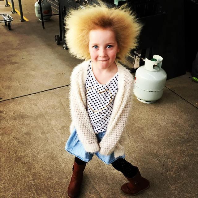 Niña con cabello rubio suéter blanco y falda