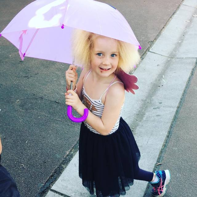 niña bajo la lluvia con paraguas en mano