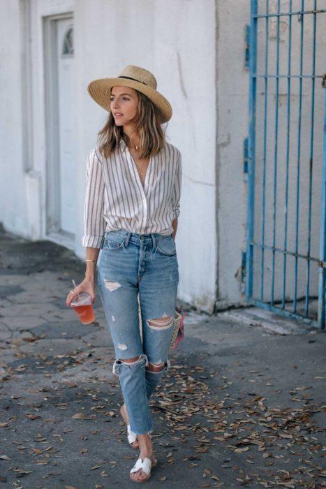Looks de primavera; chica caminando con sombrero de mimbre, blusa de rayas, pantalón de mezclilla recto y desgastado y sandalias blancas de piso; con bebida en la mano