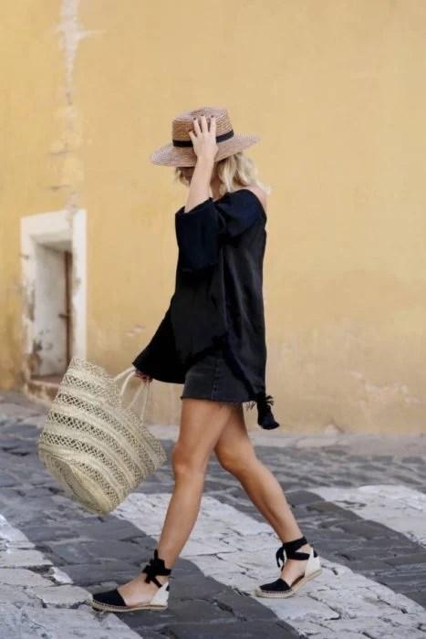 Looks de primavera; muchacha rubia con sombrero de mimbre, blusa holgada negra, shorts negros, bolsa grande de mano y sandalias negras