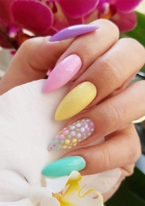 Manos de mujer con uñas estilo stiletto pintadas de colores pastel, lila, rosa, amarillo, verde