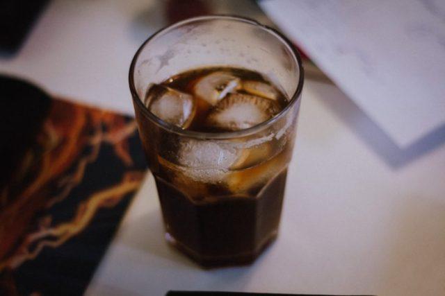 vaso de soda con hielos sobre una mesa blanca