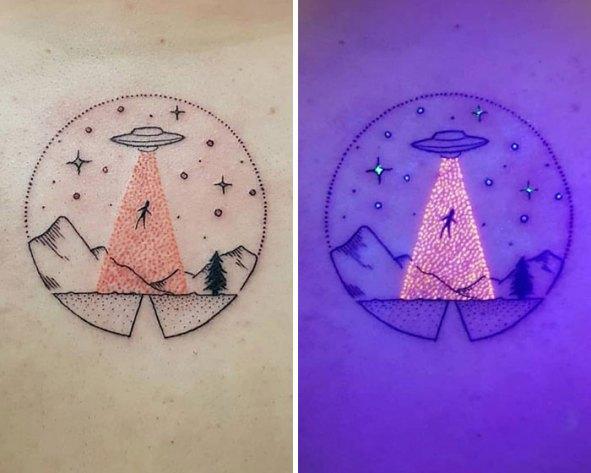 Тату с кругом, полным звезд, силуэтом гор и летающей тарелкой в похищении с ультрафиолетовым эффектом