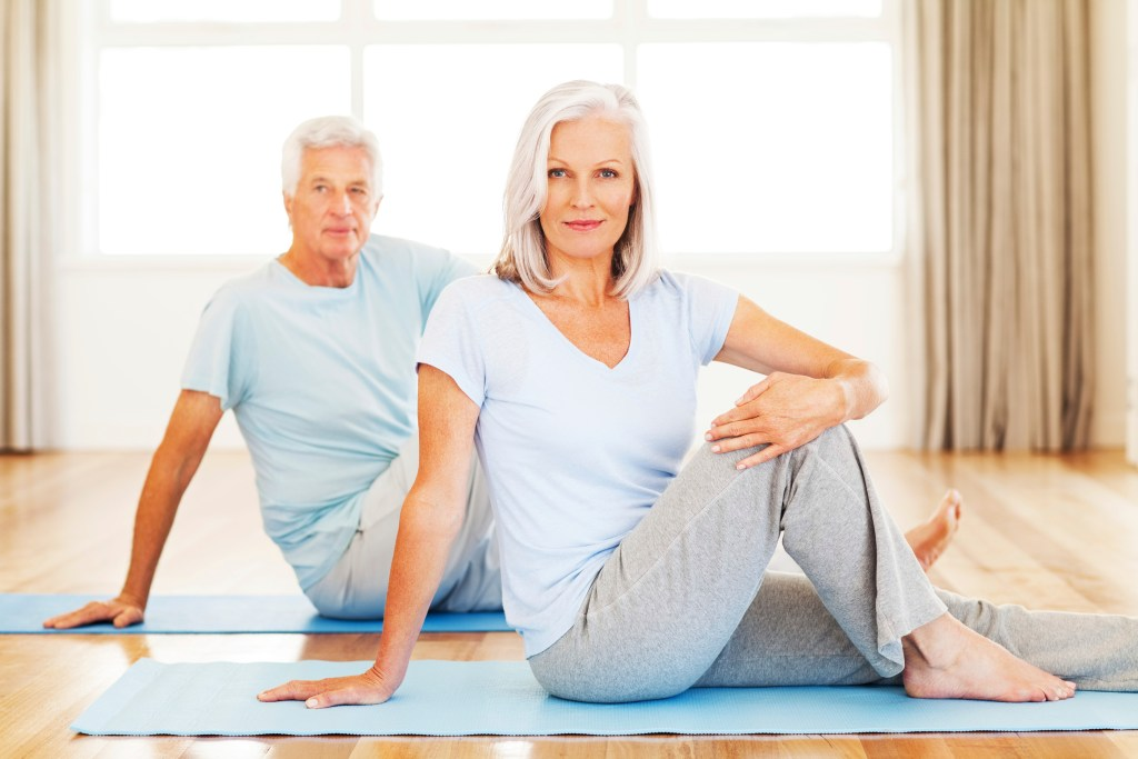 Portrait of senior woman and man practicing yoga on floor. Horizontal shot.