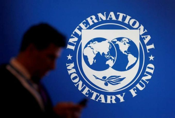 FILE PHOTO - A participant stands near a logo of IMF at the International Monetary Fund - World Bank Annual Meeting 2018 in Nusa Dua, Bali, Indonesia, October 12, 2018. REUTERS-Johannes P. Christo-File Photo