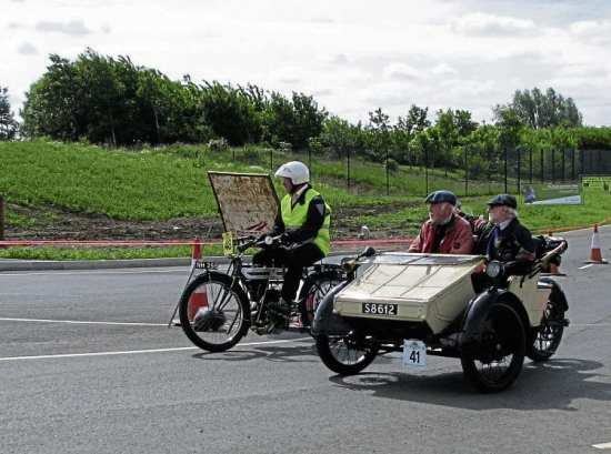 Philip Barfield (1910 Triumph) and Keith Norton and passenger in the 1911 AC Sociable tackle the roadworks outside the museum.