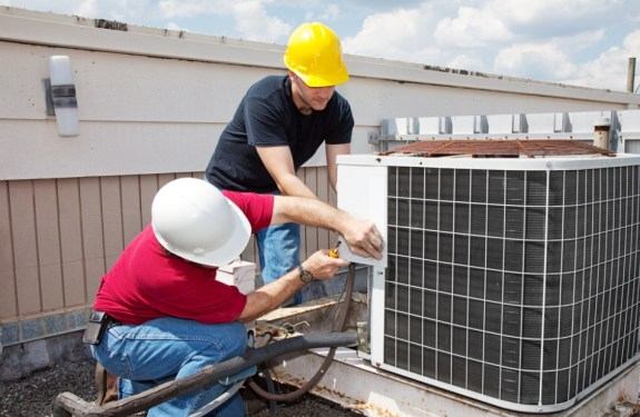 men working on a cooling system unit