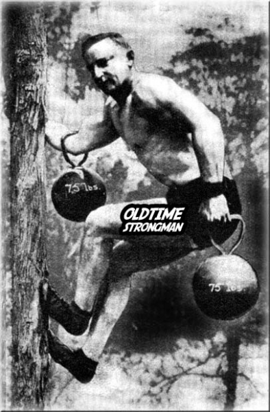 Edward W. Goodman climbs a tree with a 75 lb. kettlebell on each elbow