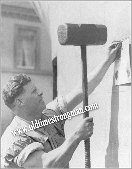 Joe Price the Blacksmith Strongman nails in a notice with a large sledgehammer