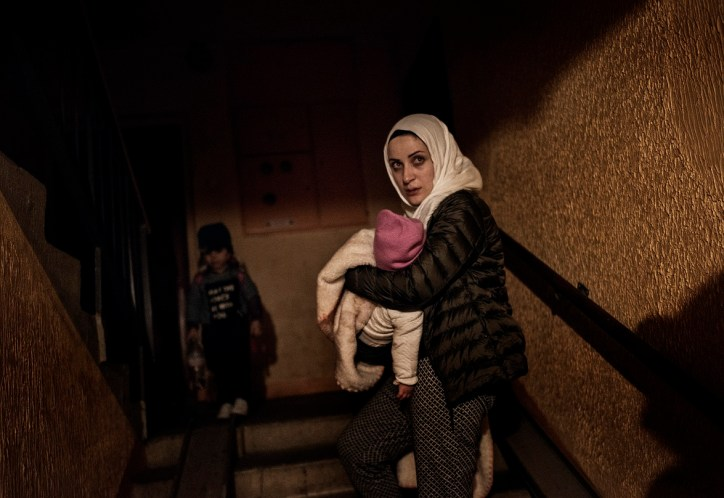 "Syrian refugee Taimaa Abazli weeps as she holds baby Heln and enters her new apartment building after a long, grueling day of travel and unheaval once again from Athens to their new home in Polva, Estonia, April 20, 2017. She says ""It's better Heln won't remember anything."" CHECK THIS QUOTE WITH ARYN The family, along with Muhannad's brother's family of Mufeed and Iyman Ateek and their two children, were relocated to a small village of 6000 people in the middle of the forest, called Polva; they feared it would be impossible to integrate and make a life in such a remote place. After over one year of traveling from war-town Syria, making their way from Turkey to Greece, waiting in greece for asylum, the family is finally relocating to Estonia. (Credit: Lynsey Addario — Verbatim for Time)"