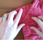 woman's hands illustrating placement on a pink sweater