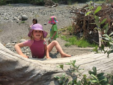 Child climbing a log