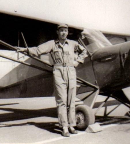 Gil Deibel posing next to a B-24 bomber