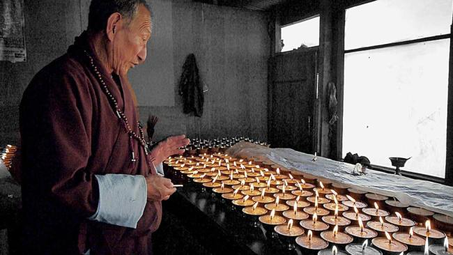 """Lighting butter lamps in Bhutan'"