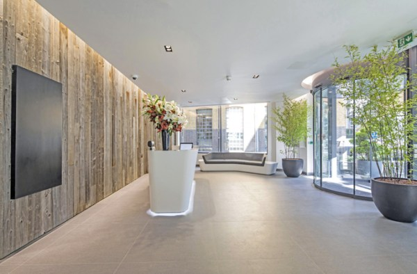 contemporary reception boasting display of flowers in a vase, plants at the glass entrance and sofa in a waiting area