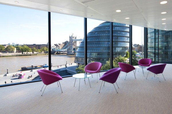 fuschia pink chairs round little glass coffee tables with a spectacular view of the neighbouring building, river Thames and the famous Tower Bridge