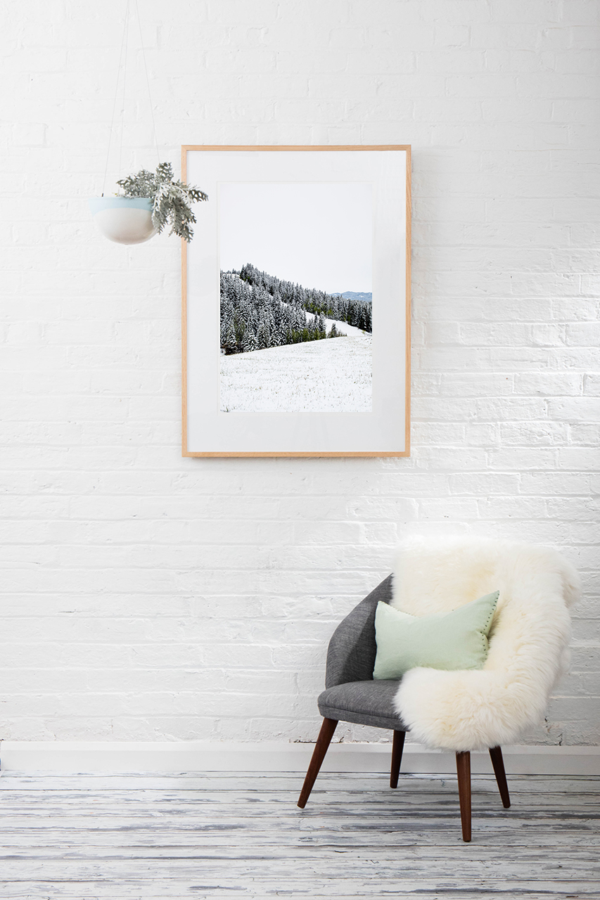 A vertical photographic landscape print of snow, moutain an trees taken in North America by Elizabeth Bull on walll above chair