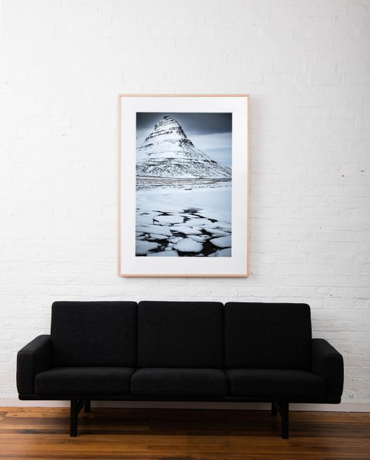 A large vertical Icelandic Landscape photographic art print of snow and mountain in blue and white framed in raw timber above sofa