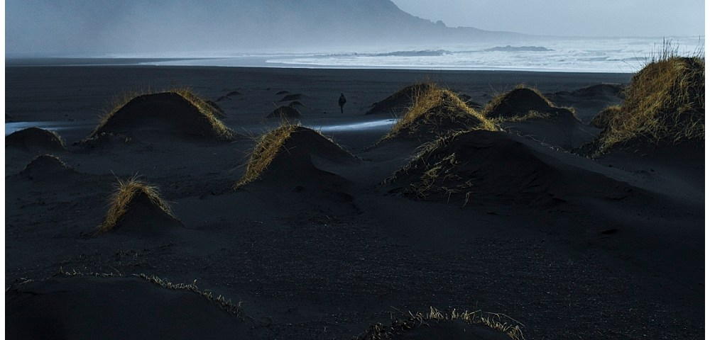 A Icelandic landscape art photograph of sea and beaches with misty mountains background. there is lone person walking on the beach