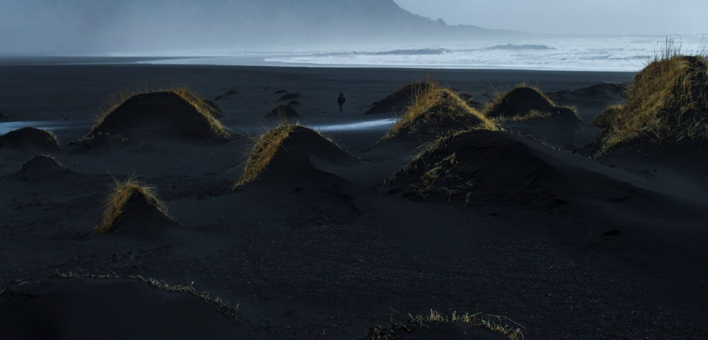 A misty photographic image of icelandic landscape of beaches, sea and mountains in shades of blue