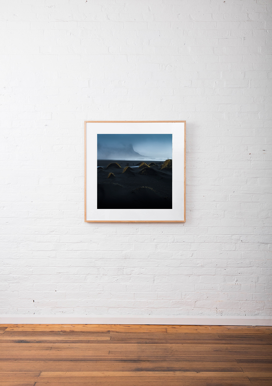 A misty photographic image of icelandic landscape of beaches, sea and mountains in shades of blue framed in raw timber on wall