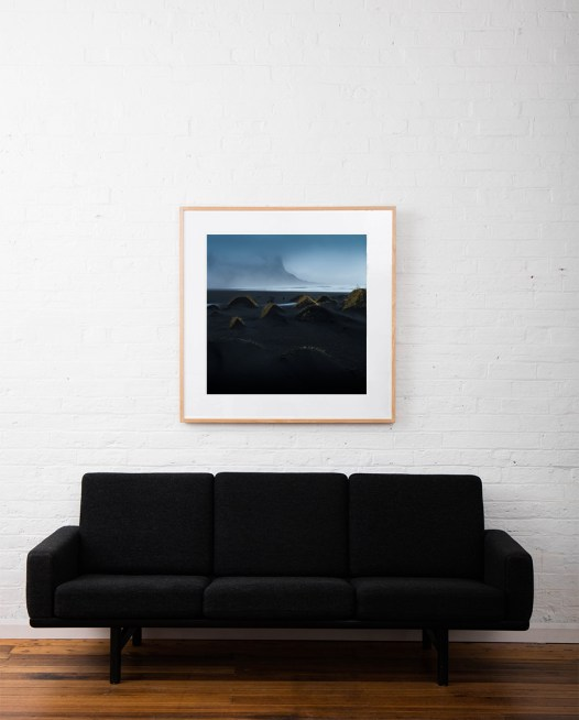 A misty photographic image of icelandic landscape of beaches, sea and mountains in shades of blue framed in raw timber on wall above sofa