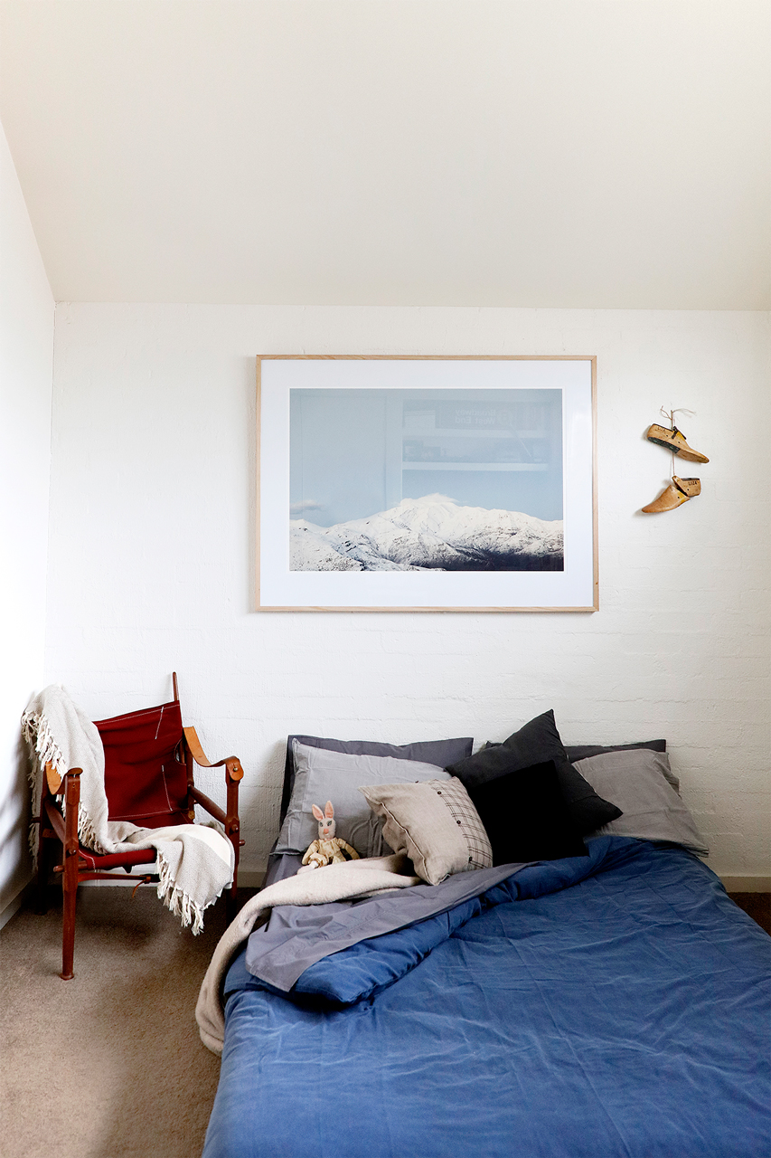 Photographic art print of mountains and snow framed in raw timber in bedroom