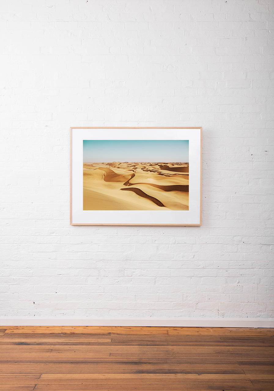 A Abstract photo of African Landscape of desert and sand in orange, yellow and blue colour framed in raw timber on white wall
