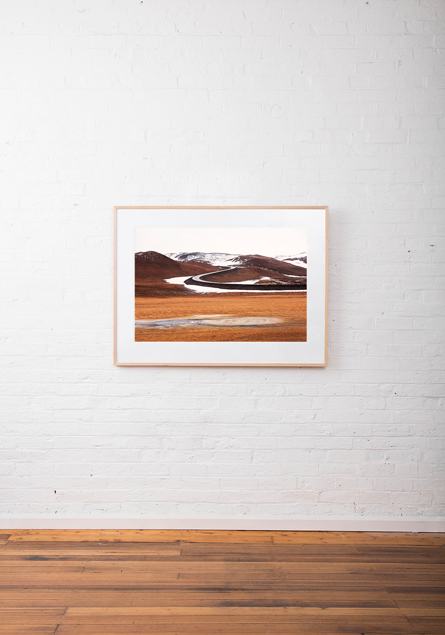 A abstract Iclandic Landscape photo of Mountains and snow in white ,brown and orange framed in raw timber on white wall