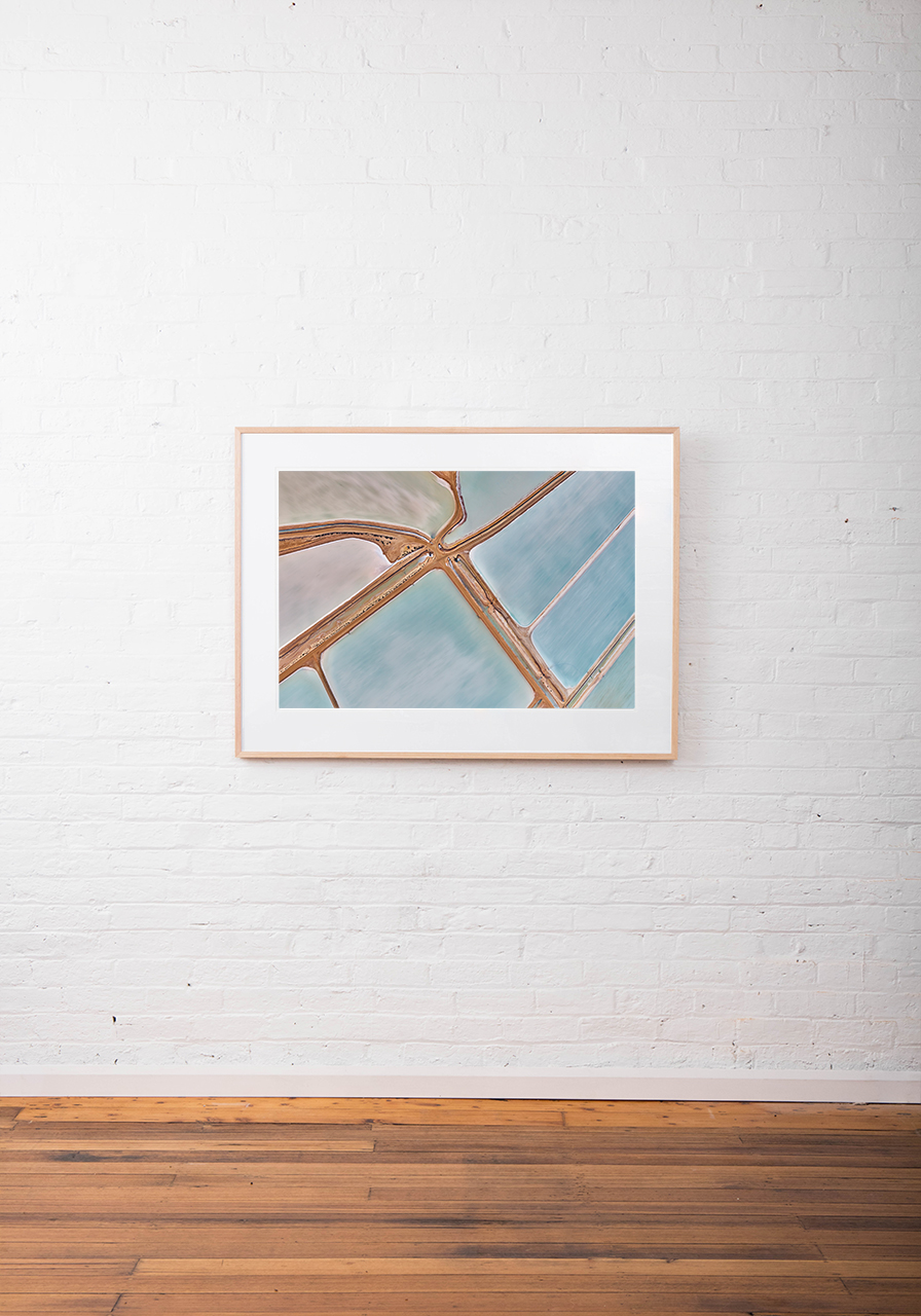 A large abstract aerial photo Water in blue and pink taken in Australia framed in raw timber on white wall