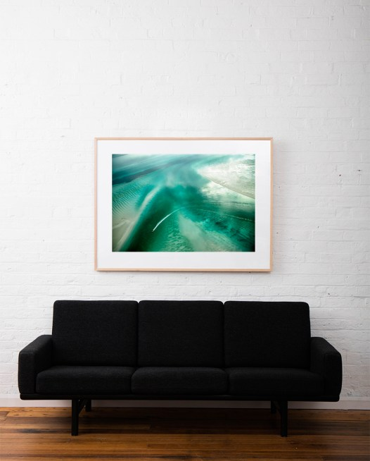 A Large Abstract Aerial Landscape photograph of water in green and white framed in raw timber on white wall above sofa