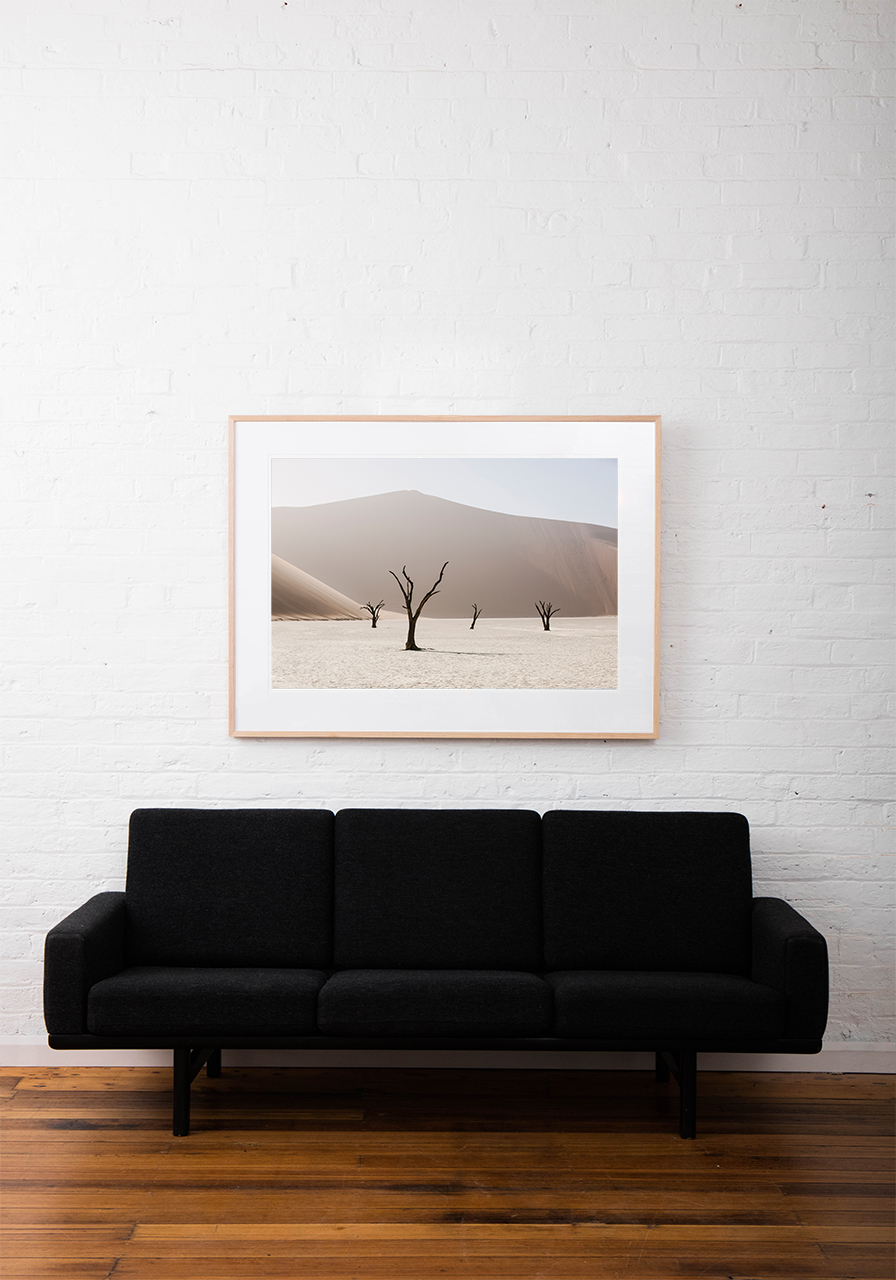 An Abstract photo of African Landscape of mountains, sand and trees in brown, pink and white framed in raw timber on white wall above sofa
