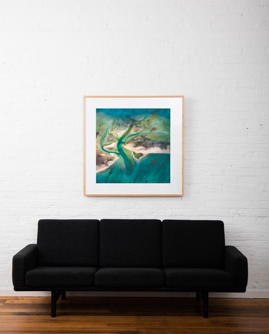 A Abstract Aerial Landscape of water in blue and green framed in raw timber hang on white wall above sofa
