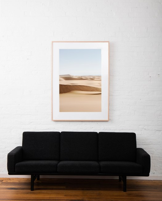 A photograph of Africa desert framed in raw timber on white wall above sofa