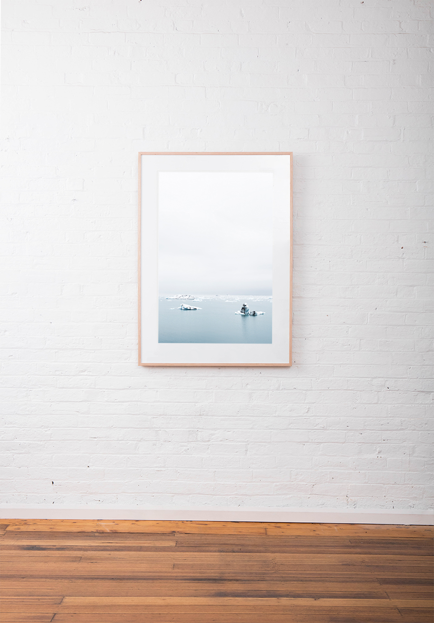 Large Print of Icelandic Landscape of glacier, snow water and sky in blue and white. Framed in raw timber on white wall