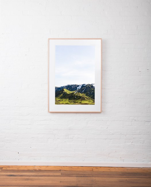 Large Icelandic Landscape photo in green and blue of glaciers, mountain, snow and blue sky.Framed in raw timber on white wall