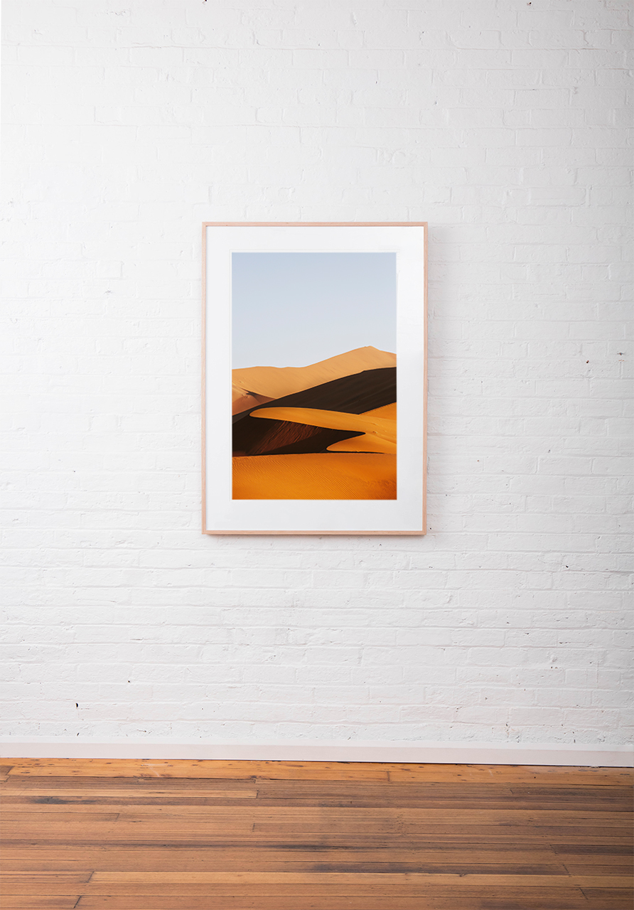 A large vertical abstract photo of African Sand Dunes framed in raw timber on white wall