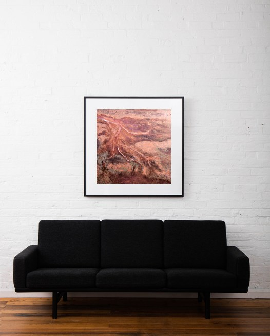 Red and pink aerial photo of the Western Australian landscape print framed in black timber frame on white wall above sofa