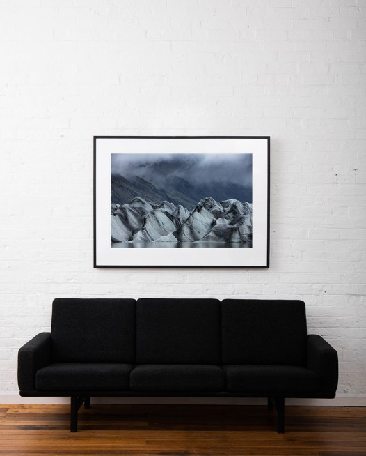 A large horizontal photo of iceberg with mountain background framed in black timber above sofa