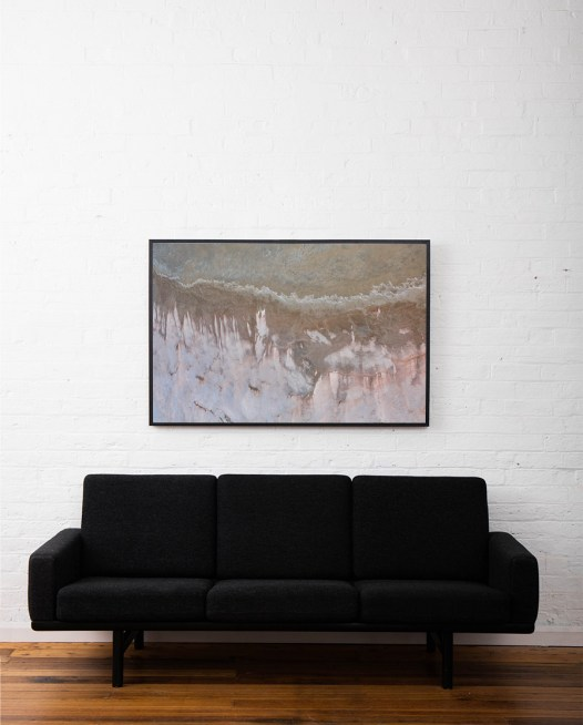 An aerial photo of inland Australia landscape in grey pink and brown color framed in black timber above sofa