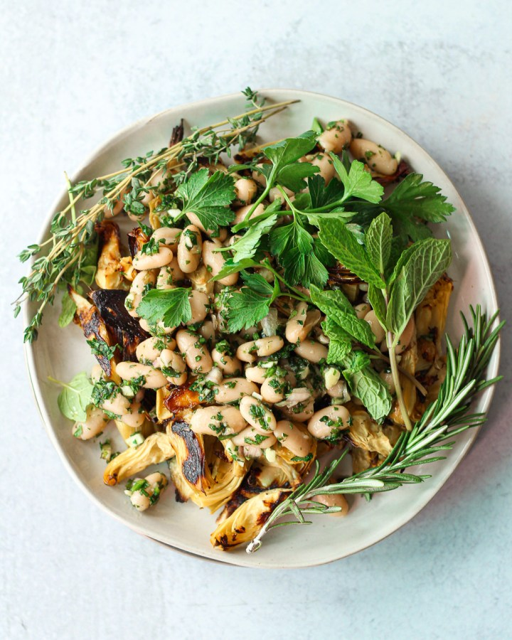 roasted artichoke bean salad on plate with herbs