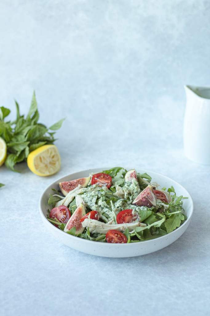 green goddess dressing on salad with herbs behind