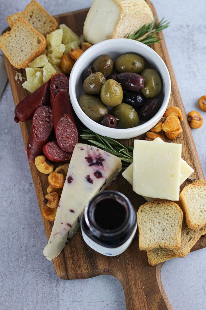 small cheese board with cheese, olives and crackers