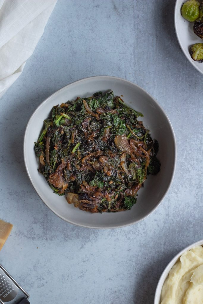 bowl of kale and caramelized onions with bowl of brussels sprouts on the side