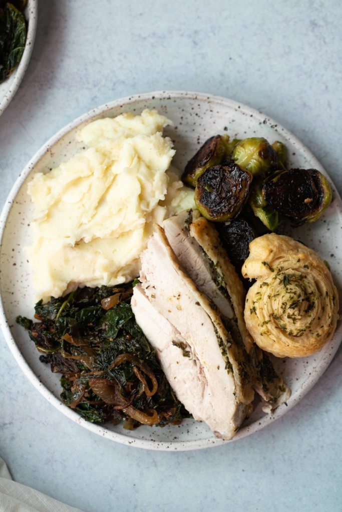 plate of thanksgiving food with mashed potatoes, turkey and brussels sprouts