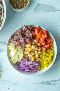 salami, peppers, onions, cheese and tomatoes in bowl for italian chopped salad